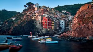 """Tourists enjoy the sunset on the cliffs of Riomaggiore - the first of the five tiny fishing villages in the enchanting """"Cinque Terre"""" (Five Lands) region of La Spezia, Italy."""